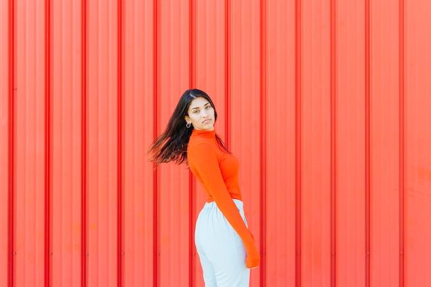Porträt der frau aufwerfend gegen roten gewölbten metallischen hintergrund