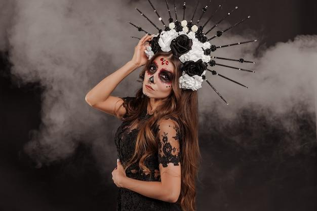 Porträt der frau bei dia de los muertos sugar skull make-up isoliert hintergrund mit rauch