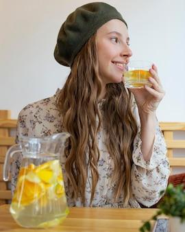 Porträt der frau, die am tisch mit limonade sitzt