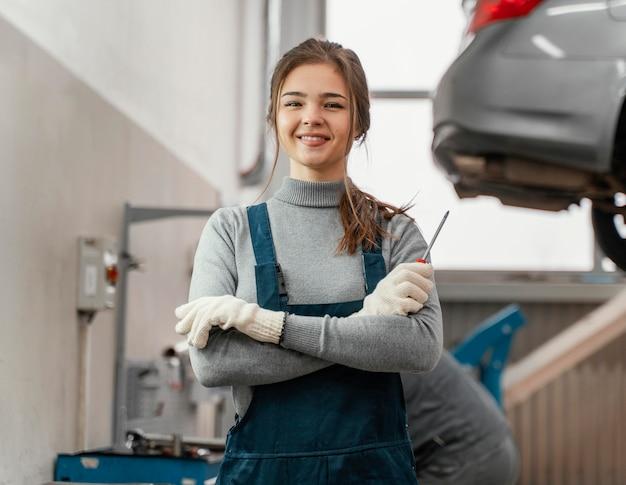 Porträt der frau, die an einem autoservice arbeitet