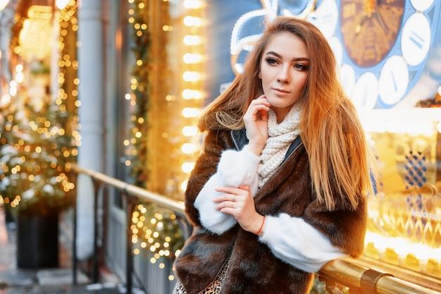 Porträt der frau, die auf der straße nahe dem elegant verzierten weihnachtsfenster aufwirft