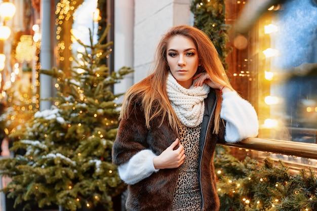 Porträt der frau, die auf der straße nahe dem verzierten weihnachtsfenster aufwirft