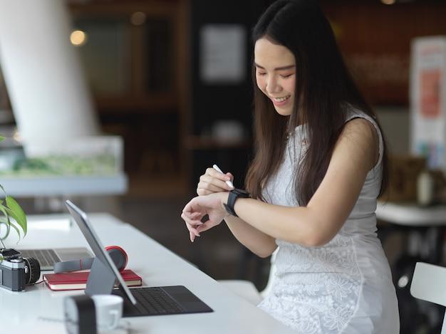 Porträt der frau, die auf smartwatch schaut, während sie im gemeinsamen arbeitsraum arbeitet