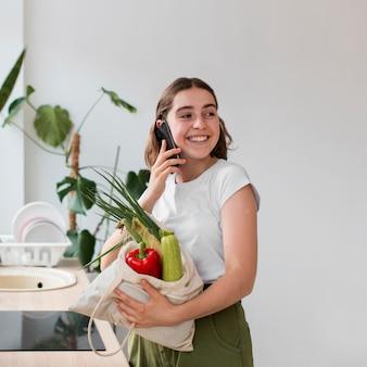 Porträt der frau, die bio-gemüse hält