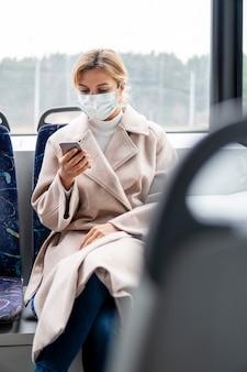 Porträt der frau, die chirurgische maske auf öffentlichen verkehrsmitteln trägt