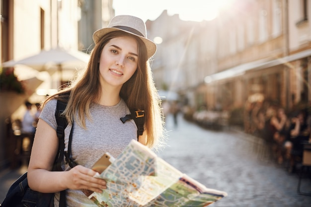 Porträt der frau, die die welt unter verwendung einer karte und einer tafel reist, die in einer kleinen europäischen stadt stehen, die kamera betrachtet.