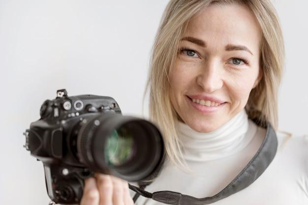 Porträt der frau, die ein kamerafoto hält