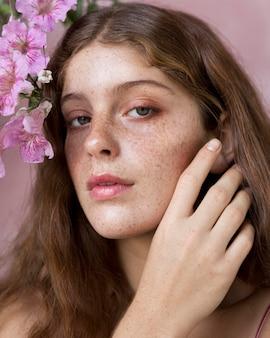 Porträt der frau, die eine rosa blume gegen ihr gesicht hält
