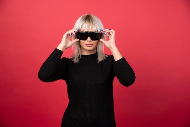 Porträt der frau, die eine schwarze brille auf einer roten wand trägt.