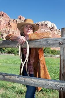 Porträt der frau, die einen cowboyhut trägt