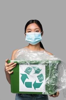 Porträt der frau, die einen papierkorb beim tragen einer medizinischen maske hält
