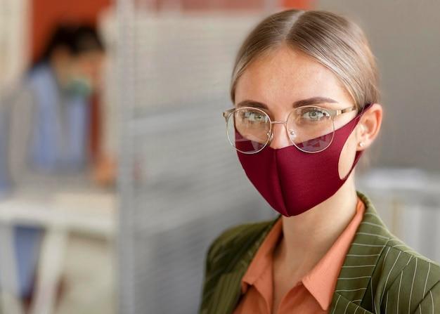 Porträt der frau, die gesichtsmaske bei der arbeit trägt