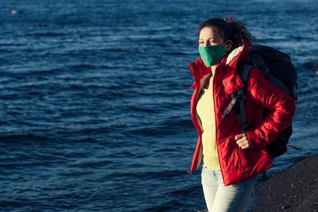Porträt der frau, die gesichtsmaske und rucksack nahe dem see trägt