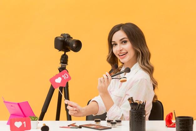 Porträt der frau, die glücklich ist, make-up-video aufzunehmen