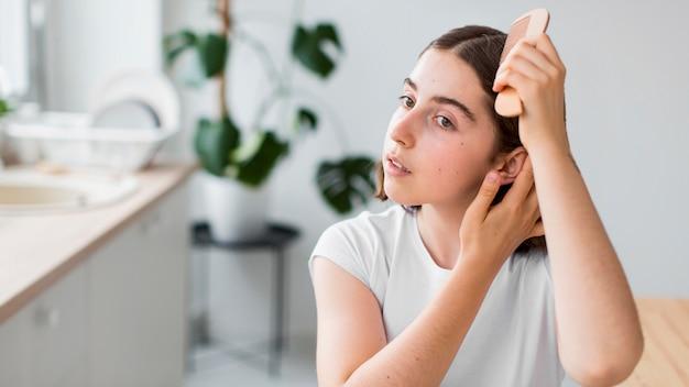 Porträt der frau, die ihre haare ordnet