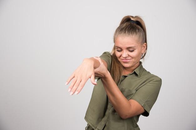 Porträt der frau, die ihre hand auf grauer wand anbietet.