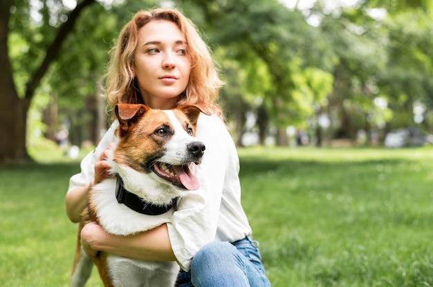 Porträt der frau, die ihren hund draußen hält