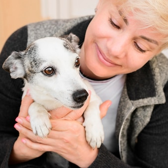 Porträt der frau, die ihren hund hält