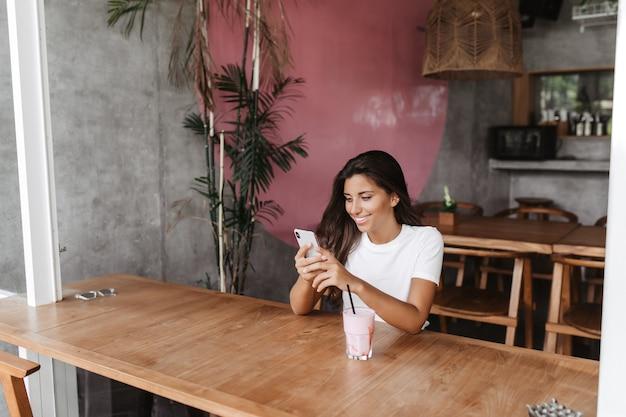 Porträt der frau, die im café sitzt und mit lächeln im smartphone plaudert