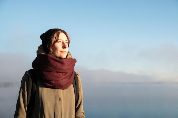 Porträt der frau, die im morgensonnenlicht steht. weiblicher wanderer, der aufgehende sonne im schönen natürlichen hintergrund genießt, der im nebel bedeckt ist