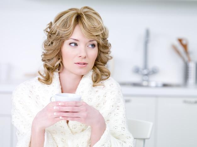 Porträt der frau, die in der küche mit tasse kaffee sitzt - drinnen