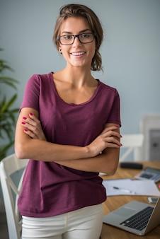 Porträt der frau, die in ihrem hausbüro arbeitet