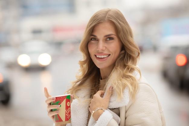 Porträt der frau, die kaffee im winter im freien trinkt.