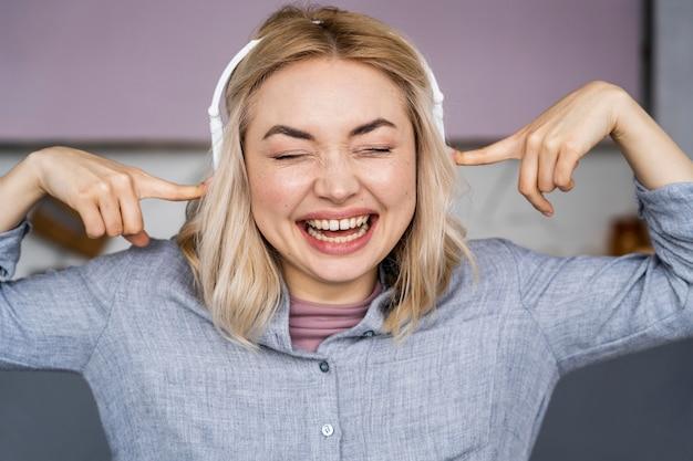 Porträt der frau, die lacht und musik über kopfhörer hört