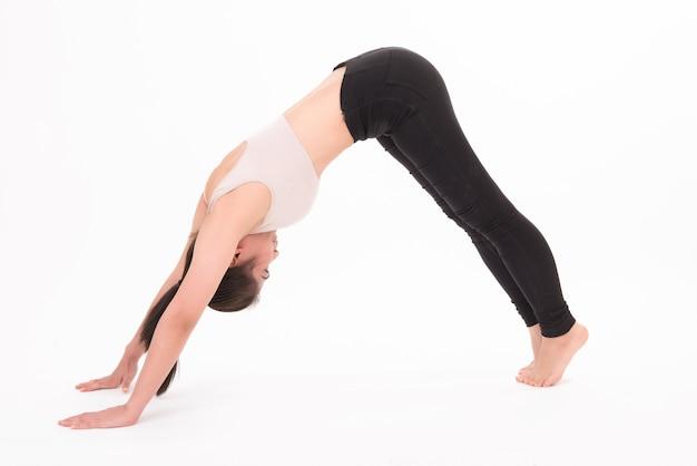 Porträt der frau, die lokalisiert auf weiß streckt. ein mädchen, das yoga auf weiß praktiziert.