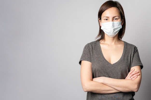 Porträt der frau, die mit chirurgischer maske aufwirft