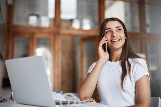 Porträt der frau, die mit ihrem freund am telefon spricht und lächelt, der spaß in einer öffentlichen bibliothek hat, die nicht schweigt.