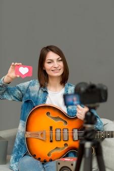 Porträt der frau, die musikvideo zu hause aufzeichnet