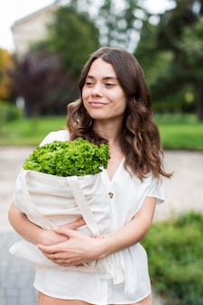 Porträt der frau, die organisches einkaufen hält