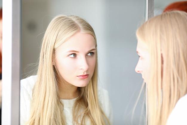 Porträt der frau, die reflexion im spiegel betrachtet. schöne frau mit angewandten make-up-überprüfungsergebnissen des stylisten vom schönheitssalon. elegante dame mit blonden haaren