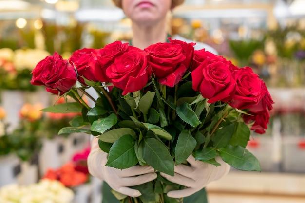 Porträt der frau, die sammlung der roten rosen hält