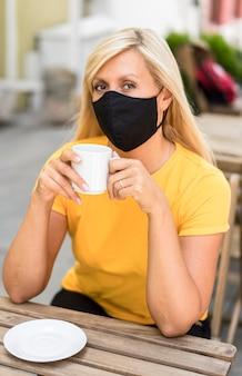Porträt der frau, die stoffmaske trägt, die einen kaffee hält