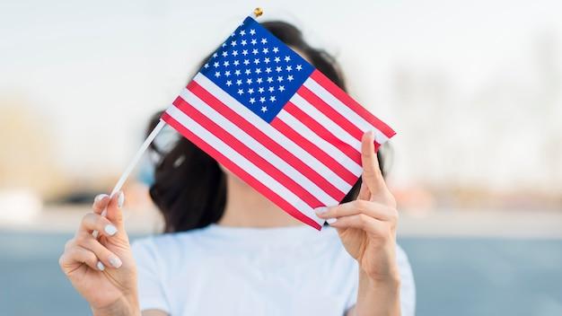 Porträt der frau, die usa-flagge über gesicht hält