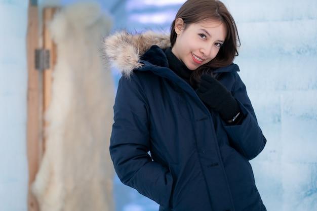 Porträt der frau, die warmen mantel mit pelzhaube trägt, spaß im winter habend. wand aus eisblöcken