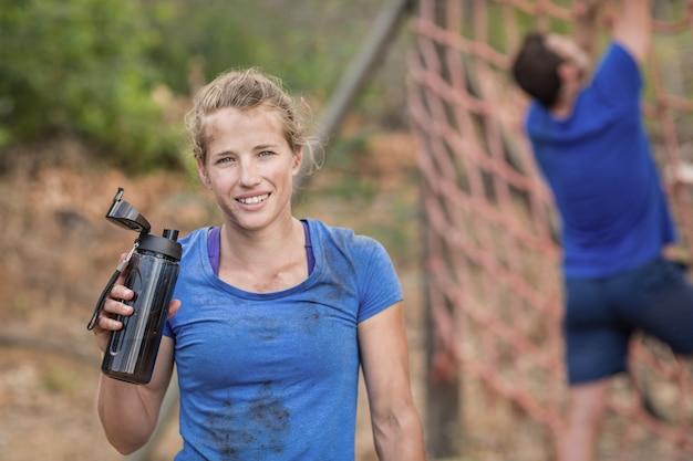 Porträt der frau, die wasserflasche während des hindernislaufs im bootcamp hält