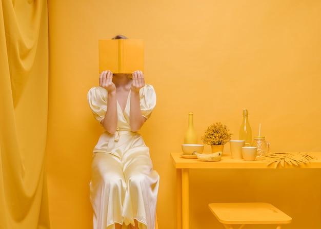 Porträt der frau ein buch in einer gelben szene lesend