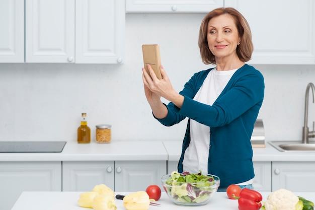 Porträt der frau ein selfie in der küche nehmend