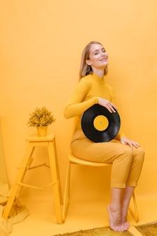 Porträt der frau ein vinyl in einer gelben szene halten