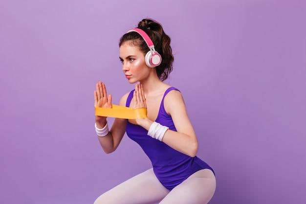Porträt der frau im bodysuit und in den leggings, die kniebeugen mit gummiband tun