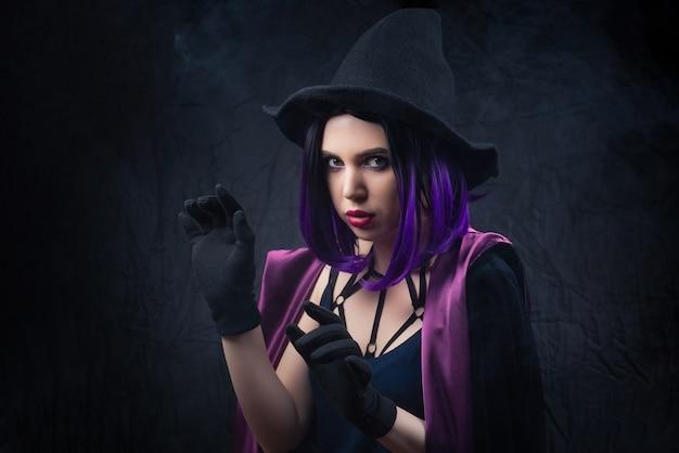 Porträt der frau im halloween-kostüm mit hellem make-up und lila haaren