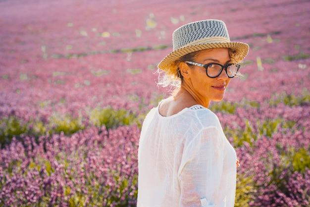 Porträt der frau im hut, der auf lavendelblumenfeld steht. schöne frau in den brillen, die beim stehen auf dem feld lächelt. frau, die vom landwirtschaftlichen lavendelblumenfeld über die schulter schaut