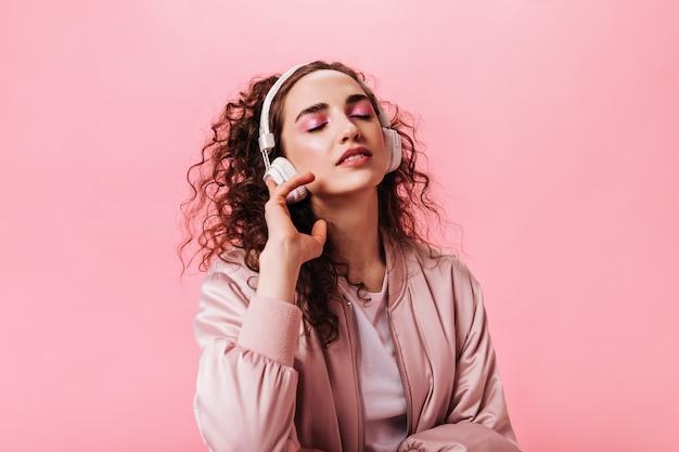 Porträt der frau im rosa outfit, das musik in den kopfhörern genießt