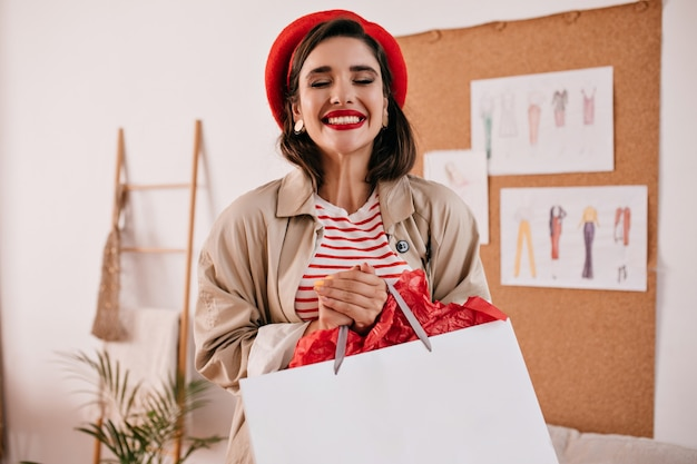 Porträt der frau im roten hut und im gestreiften hemd stellt glücklich mit einkaufstasche auf. nettes mädchen mit hellem lippenstift in baskenmütze und beigem mantel lächelt.