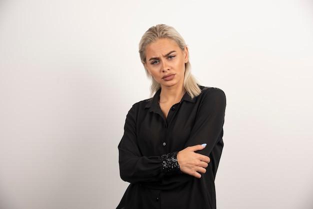 Porträt der frau im schwarzen hemd, das auf weißem hintergrund aufwirft. hochwertiges foto