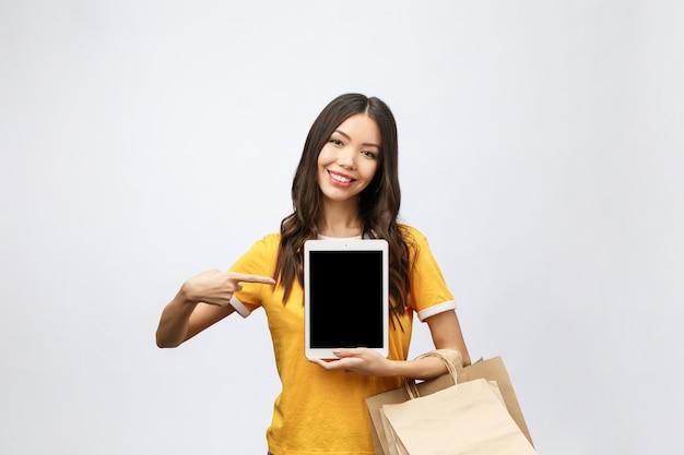 Porträt der frau im sommerkleid, das paketbeutel mit einkäufen nach dem online-einkauf hält