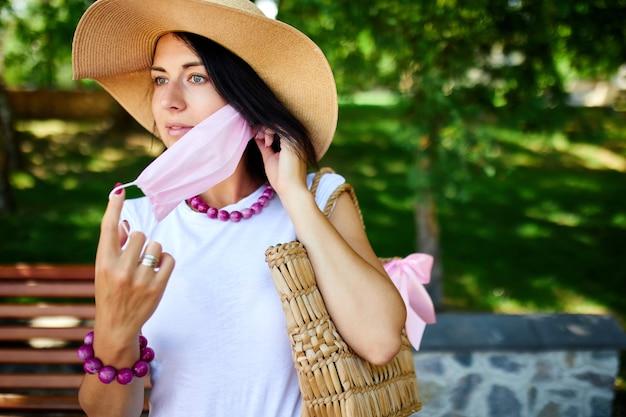 Porträt der frau im strohhut nimmt rosa schutzmaske ab, im park im freien in der stadt, konzept selbstpflege, leben während coronavirus-pandemie, über quarantäne